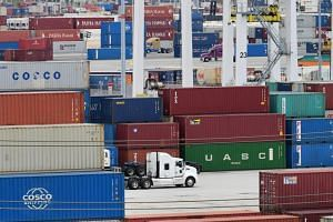 Container trucks make their way past stacked containers at the Port of Los Angeles on June 18, 2019. Goldman economists noted a substantial pick up in exports to the US from Asian economies including Taiwan, Vietnam and India that's effectively cance