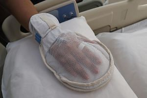 The new mitten has a zip to allow nurses to access a patient's fingers to take blood tests or check his vital signs.