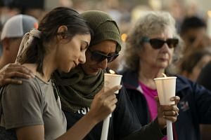 Hina Moheyuddin (left) and Noshaba Afzal hold candles during a vigil for the victims.