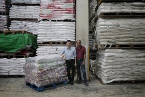 See Hoy Chan operations manager Lim Ek Kwong and Singapore General Rice Importers Association chairman Michael Hiu (far right) say firms that import Thai rice are feeling the pinch from the rising baht. Mr Lim expects to pay US$1,300 (S$1,779) for a