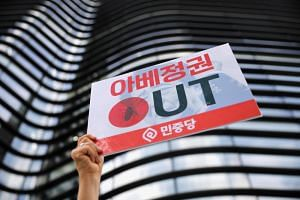 "A protester holds up a sign reading ""Abe regime out"" during an anti-Japan rally in front of the Japanese embassy in Seoul on Aug 2, 2019."