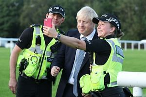 Johnson has a selfie taken with police officers as he arrives to meet emergency crews in Whaley Bridge.