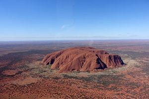 A sweeping view of Uluru in the desert. This picture was taken during a helicopter ride.