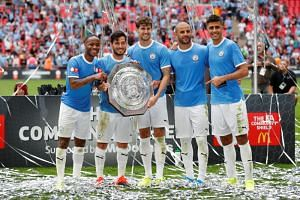 Manchester City's Raheem Sterling, David Silva, John Stones, Kyle Walker and Rodri pose as they celebrate winning the FA Community Shield with the trophy.
