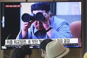 In this file photo taken on Aug 2, people stand by a TV screen showing a file footage of North Korean leader Kim Jong Un during a news program at the Seoul Railway Station.