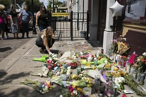A mourner pays respects at a makeshift memorial near the scene of a mass shooting that occurred on Aug 3 in Oregon, Ohio.