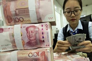 A bank employee counts US dollars next to a stack of Chinese yuan in eastern China's Jiangsu province. Yesterday's developments mean currency issues are now being dragged into the debate on trade and even monetary policy. PHOTO: ASSOCIATED PRESS