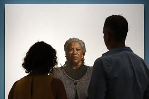 Visitors view a portrait of Nobel laureate Toni Morrison, painted by the artist Robert McCurdy at the National Portrait Gallery in Washington on Aug 6, 2019.