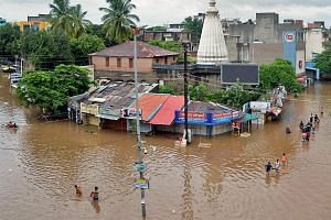 In this picture taken on Aug 6, 2019 people wade through a flooded street in Sangli, Maharashtra. The tally of dead in the floods was 25 in the western state of Maharashtra.