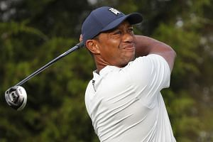 Woods tees off on the 12th hole during the first round.