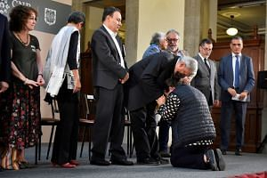 Mexico's President Andres Manuel Lopez Obrador comforts a woman who knelt down to ask him for help to look for her missing relative, during an event in June 2019 in which Mexico's government identified thousands of human remains accumulated in morgue
