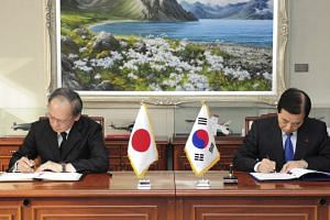 In this photo taken on Nov 23, 2016, South Korean Defense Minister Han Min Koo and Japanese Ambassador to South Korea Yasumasa Nagamine sign the General Security of Military Information Agreement.