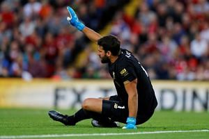 Liverpool's Alisson reacts after sustaining an injury.