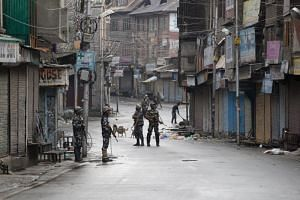 Indian paramilitary soldiers standing guard on a deserted street during curfew in Srinagar, Kashmir, on Aug 8, 2019.