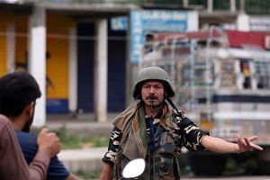 An Indian security forces soldier stopping two people on a motorbike in Srinagar, Kashmir, on Aug 9, 2019.