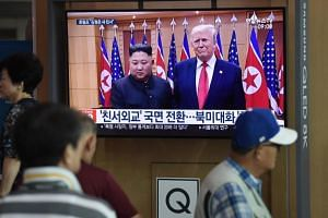People watching a news report showing file footage of US President Donald Trump and North Korean leader Kim Jong Un, at a train station in Seoul on Aug 10, 2019.