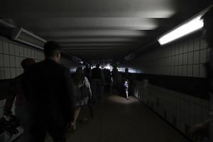 People walk in near darkness at Clapham Junction station during a power cut in London on August 9, 2019.