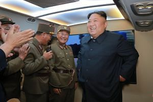 In an Aug 7, 2019 photo, North Korean leader Kim Jong Un (right) watches the firing of a new-type of tactical guided missile.