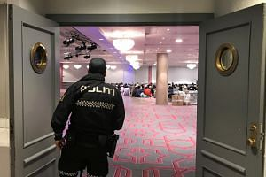 A Norwegian police officer looks on as people gather before morning prayer in Thon Oslofjord hotel in Sandvika, Norway, on Aug 11, 2019.