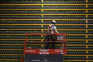 In a photo taken on March 19, 2018, a technician inspects the backside of bitcoin mining at Bitfarms in Saint Hyacinthe, Quebec.