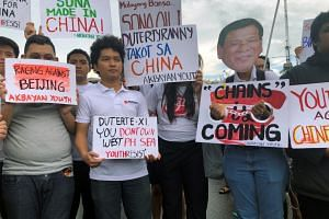 In a photo taken on July 22, 2019, Filipino student activists hold placards against China during a protest against Duterte's annual State of the Nation Address in Manila, Philippines.