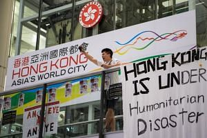 A protester raises his fist and chants as protesters occupy Hong Kong Chek Lap Kok International Airport in Hong Kong, on August 12, 2019.