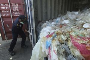 In a photo taken on July 29, an Indonesian officer opens a container full with illegal imported plastics waste in Batam.