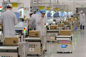 In a photo taken on March 25, employees work on a mobile phone production line at Huawei's factory campus in Dongguan, China.