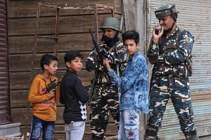 Children play with toy guns next to Indian security force personnel during restrictions after the scrapping of the special constitutional status for Kashmir.