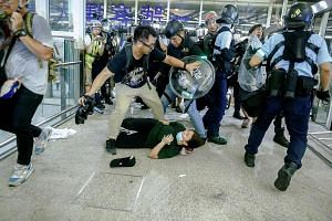 Above: A tourist passing her luggage to security guards as she tried to enter a departure gate yesterday amid another demonstration by anti-government protesters at Hong Kong International Airport. PHOTO: AGENCE FRANCE-PRESSE Right: Riot police tryin