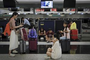 Travellers at closed check-in counters as protesters remain at the Hong Kong international airport on Aug 12, 2019.