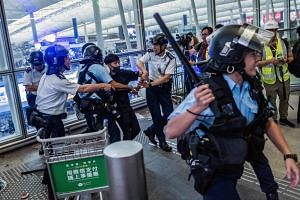 In a photo taken on Aug 13, 2019, a protestor is taken into custody at the Hong Kong International Airport.