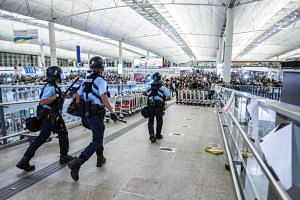 Demonstrators and riot police clashed at Hong Kong's airport late on Tuesday (Aug 13) after flights were cancelled for a second day.