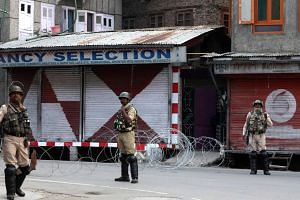 Tens of thousands of troop reinforcements have been deployed to the main city of Srinagar and other towns and villages, turning the picturesque city into a deserted warren of barbed wire and barricades.