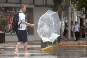 A man making his way amid strong wind caused by severe tropical storm Krosa, in Miyazaki, Japan, on Aug 14, 2019.