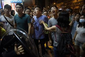 Local residents react to the arrest of a suspected anti-government protester by the police in Hong Kong on Aug 11, 2019.