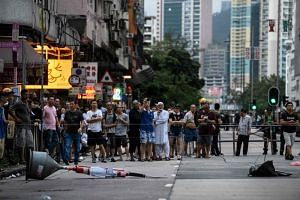 Residents gather after tear gas was fired at protesters in Hong Kong's Sham Shui Po district on Aug 11, 2019.