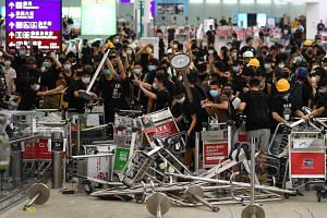 Protesters blocking the entrance to airport terminals after a scuffle with police at Hong Kong's international airport on Aug 13, 2019.