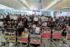 Hong Kong protesters staging a sit-in at Hong Kong International Airport on Aug 13, 2019. Singapore's MFA has issued a travel advisory asking Singaporeans to defer all non-essential travel to the island, on Aug 16.