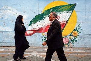 People walk past a mural depicting an Iranian national flag in a street in the Iranian capital Teheran.