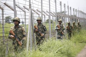 In a photo taken on Aug 14, India's Border Security Force soldiers patrol along the India-Pakistan border in Akhnoor near Jammu, after the Indian government stripped Jammu and Kashmir of its autonomy.