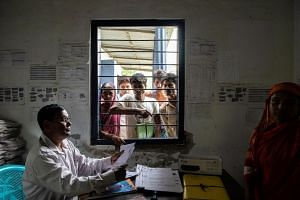 In a photo taken on July 19, 2019, a government official in Kharupetia, in the Indian state of Assam, collects documents from people hoping to be included on an official list of Indian citizens.
