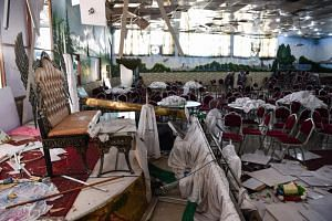 In a photo taken on Aug 18, 2019, Afghan men investigate a wedding hall after a deadly bomb blast in Kabul.