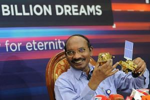 Chairman of the Indian Space Research Organisation (ISRO) K. Sivan holds up a model of the Chandrayaan 2 spacecraft during a press conference at the ISRO headquarters in Bangalore on Aug 20, 2019.