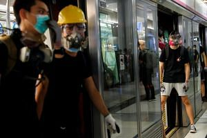 Protesters blocking the doors of a Mass Transit Railway train at Yuen Long station, Hong Kong, on Aug 21, 2019. Chinese state-backed media outlets accused Hong Kong's Mass Transit Railway company on Aug 22 of abetting protesters by offering them a fr