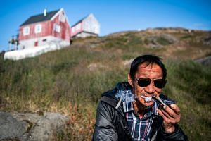 A man smokes a pipe in the town of Kulusuk in Greenland.