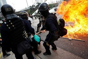 Hong Kong riot police detain a demonstrator as they clash during a protest in Hong Kong on Aug 24.