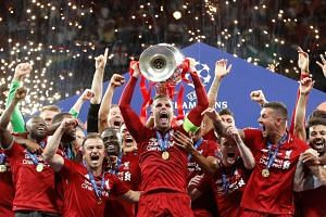 Liverpool's Jordan Henderson celebrates with the trophy and teammates after winning the Champions League Final against Tottenham, on June 1, 2019.