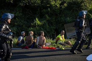 From left: Anti-G-7 activists being detained by French national police near Hendaye, France, on Friday; demonstrators carrying rubber boats, in a reference to migrants crossing the Mediterranean, during a protest in Hendaye yesterday; and a protester