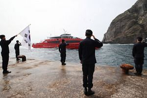 South Korean patrol guards offer a salute to a passenger ship, which failed to land due to high waves on the easternmost islets of Dokdo, called Takeshima in Japan, on Aug 18, 2019. Seoul and Tokyo have long been at loggerheads over the sovereignty o